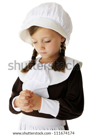 """Closeup of a pretty young elementary """"pilgrim"""" girl in prayer.  On a white background. - stock photo"""