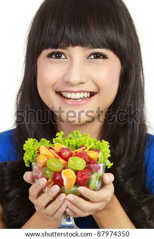 Closeup of a pretty young lady eating fruit salad in isolated white background