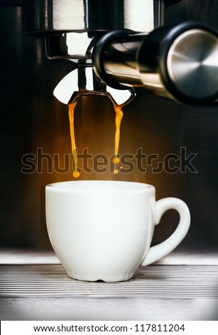 Closeup of a professional stainless steel coffee machine pouring freshly brewed aromatic espresso coffee into a plain white ceramic cup - stock photo
