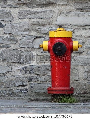 closeup of a red and yellow fire hydrant with a rock wall background - stock photo