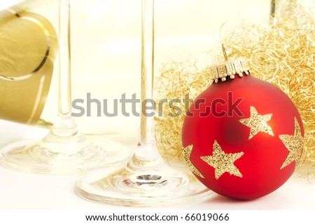 closeup of a red dull christmas ball with champagne glass bottom in front of a champagne bottle - stock photo
