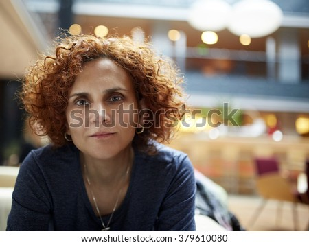 Closeup of a redhead woman in a restaurant with selective focus - stock photo