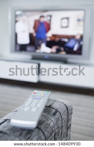 Closeup of a remote control with blurred television in the background - stock photo