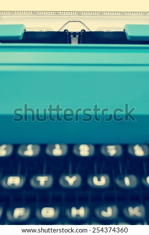closeup of a retro blue typewriter with a blank page in its roller, with a filter effect - stock photo
