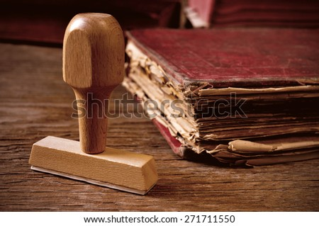 closeup of a rubber stamp and a worn-out old book, on a rustic wooden table - stock photo