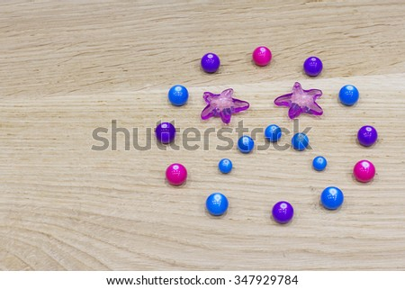Closeup of a sad smiley made of colorful beads on wooden surface - stock photo