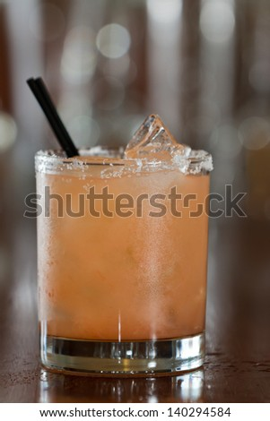 closeup of a salty dog drink served in a short glass on a busy out of focus bar - stock photo