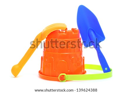 closeup of a sand / beach toy set with a pail, shovel and rake of different colors on a white background - stock photo