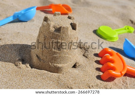 closeup of a sandcastle and some toy shovels on the sand of a beach - stock photo