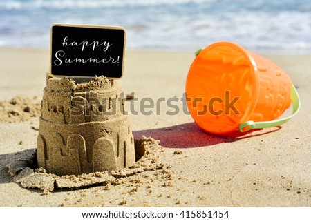 closeup of a sandcastle on the sand of a beach topped with a black signboard with the text happy summer written in it, and an orange beach pail next to it - stock photo