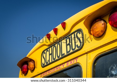 Closeup of a school bus from the back with the stop lights and the emergency exit visible - stock photo