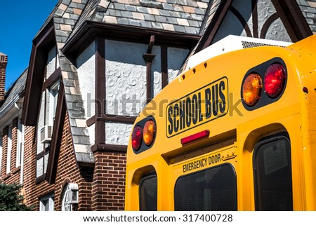 Closeup of a school bus from the back with the stop lights and the emergency exit visible in a residential area with a house in the background - stock photo