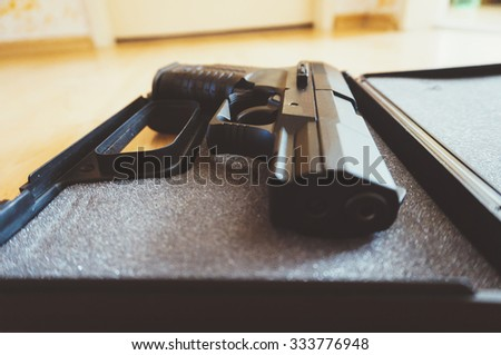 Closeup of a semi-automatic pistol in a open box - stock photo