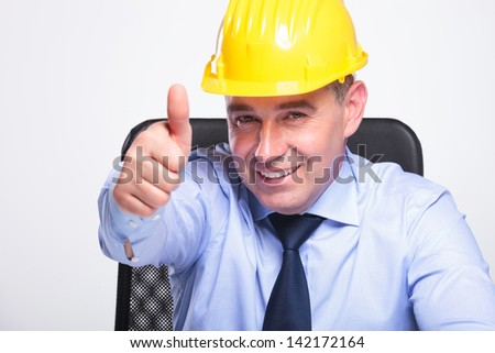 closeup of a senior business man with helmet sitting on a chair and showing the thumb up gesture while smiling to the camera. on gray background