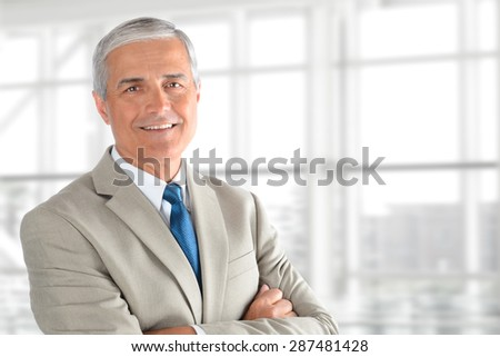 Closeup of a senior businessman with his arms folded in an office interior. Horizontal format with copy space. - stock photo