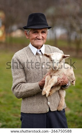 Closeup of a senior man holding a cute baby goat outdoor - stock photo