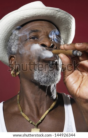 Closeup of a senior man in fedora smoking cigar against red background - stock photo