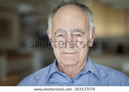 Closeup Of A Senior Man Smiling At The Camera. He is standing and relaxing in the kitchen at home. - stock photo