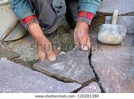 closeup of a senior, paving a patio with natural stones - stock photo