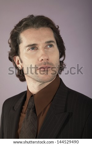 Closeup of a serious young businessman looking away against purple background - stock photo