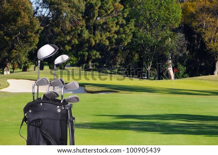 Closeup of a set of golf clubs in a bag on the fairway of a Golf Course on a sunny day.