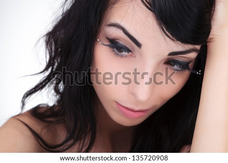 closeup of a sexy young fashion woman looking with a thoughtful look away from the camera. on gray background - stock photo