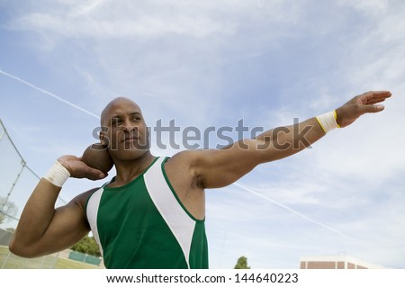 Closeup of a shot putter preparing to toss shot put against the sky