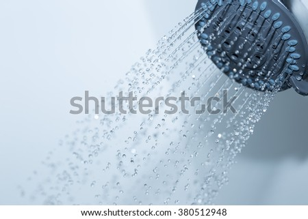 Closeup of a shower head with sprinkling water, blue toned photo.