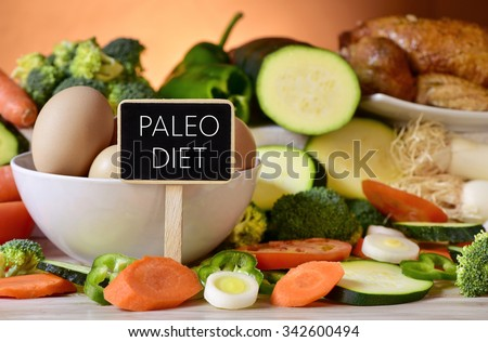 closeup of a signboard with the text paleo diet on a table full of different raw vegetables, a bowl with some chicken eggs and a chicken - stock photo