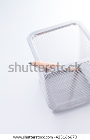 Closeup of a single pencil in a wire pencil cup on white background , one point focus - stock photo