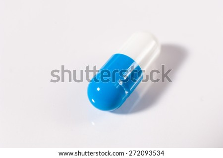 Closeup of a single pill over white background.