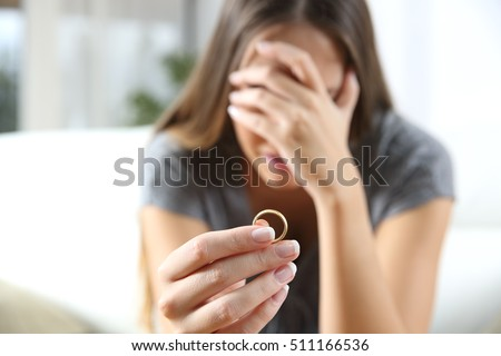 Closeup of a single sad wife after divorce lamenting holding the wedding ring in a house interior