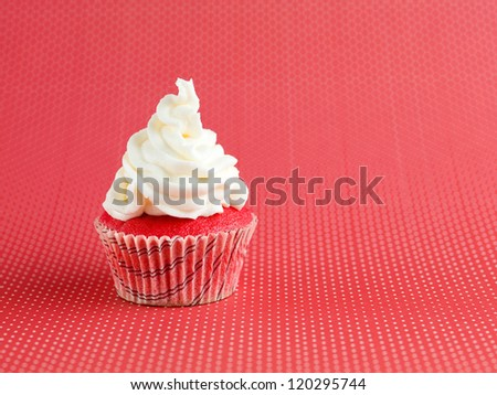 closeup of a single tiny velvet cupcake, with white icing on top, isolated on red polka dots background - stock photo