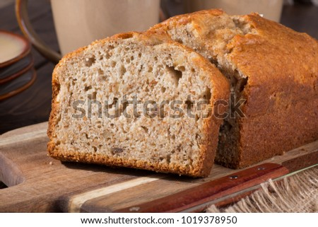 Closeup of a slice of banana nut bread on a wooden cutting board