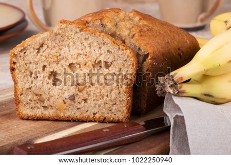 Closeup of a slice of banana nut bread on a wooden cutting board with bananas on the side