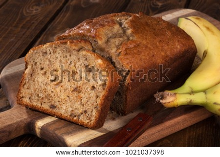 Closeup of a slice of banana nut bread on a wooden cutting board with two bananas on the side