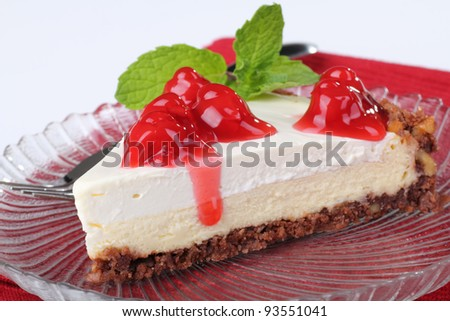 Closeup of a slice of cheesecake topped with cherries - stock photo