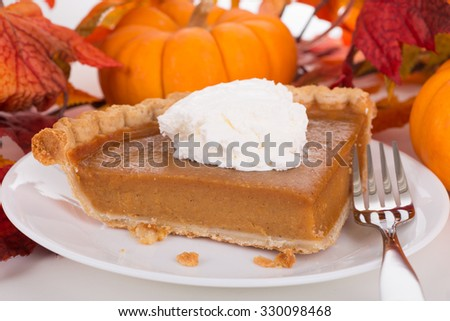 Closeup of a slice of pumpkin pie with colorful autumn decorations - stock photo
