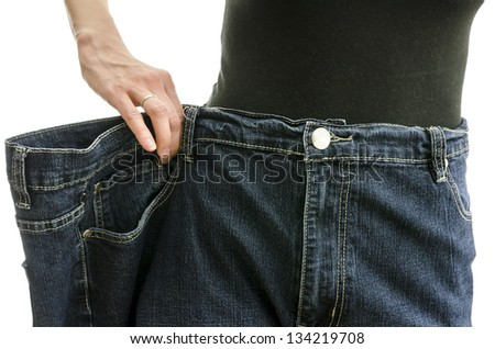 Closeup of a slim woman waist in over sized pants after losing a lot of weight. Over white background. - stock photo