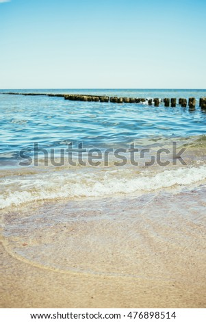 Closeup of a small wave on the beach with a wooden breakwater in the background.