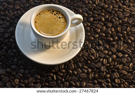 Closeup of a small white cup of freshly brewed coffee with coffee beans in background