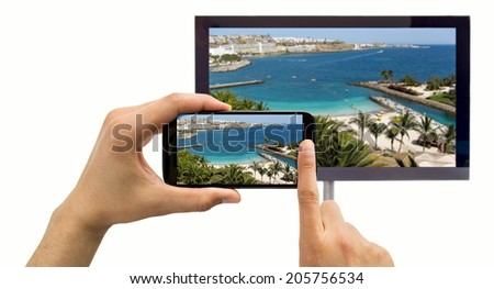 closeup of a smartphone connected to a tv and envisioning photos in networking - stock photo