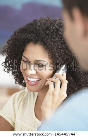 Closeup of a smiling businesswoman using cellphone in a meeting - stock photo