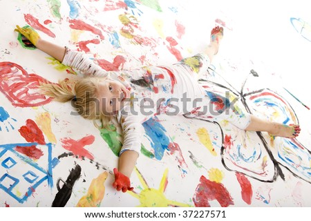 Closeup of a smiling child full of paint and laying on a painted floor - stock photo