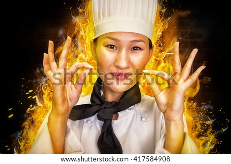Closeup of a smiling female cook gesturing okay sign against dark background - stock photo