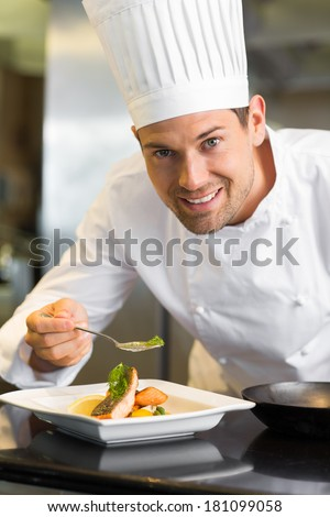 Closeup of a smiling male chef garnishing food in the kitchen - stock photo