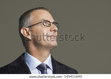 Closeup of a smiling middle aged businessman in glasses smiling against gray background - stock photo