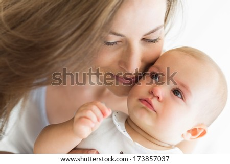 Closeup of a smiling mother and baby over white background