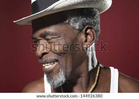 Closeup of a smiling senior man in fedora against red background - stock photo