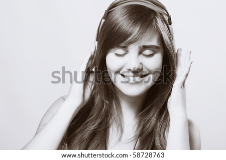Closeup of a smiling young woman listening music - stock photo